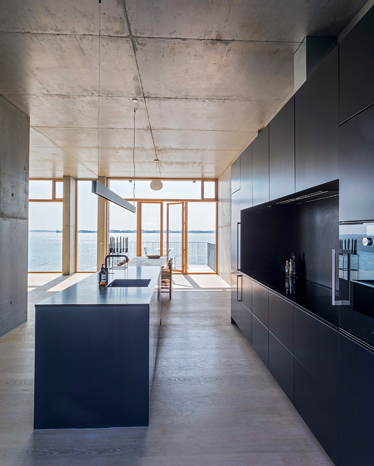 The architect couple ended up choosing the black Form 2 kitchen from Multiform, which stands out beautifully against the concrete walls and solid oak floors.